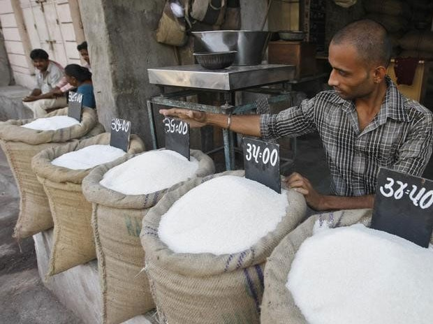 A vendor arranges a price tag over a sack filled with sugar at a wholesale vegetable market in Ahmedabad September 11, 2013. REUTERS