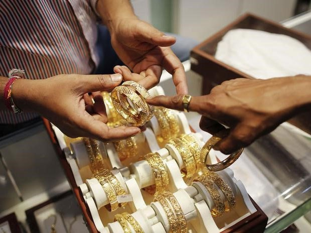 An employee shows gold bangles to a customer at a jewellery showroom on the occasion of Dhanteras, a Hindu festival associated with Lakshmi, the goddess of wealth, at a market in Mumbai.