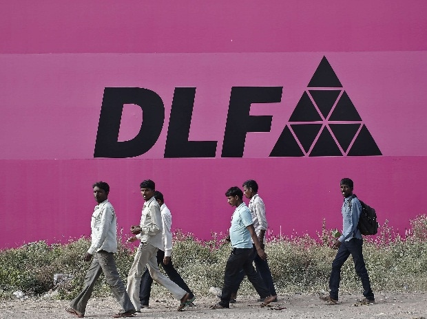 Workers walk past a billboard of DLF Ltd at Gurgaon on the outskirts of New Delhi