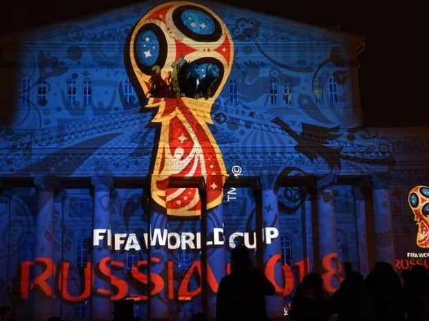 In this file photo, people watch as the facade of the historical Bolshoi Theatre is illuminated with the official emblem of the 2018 FIFA World Cup in central Moscow.