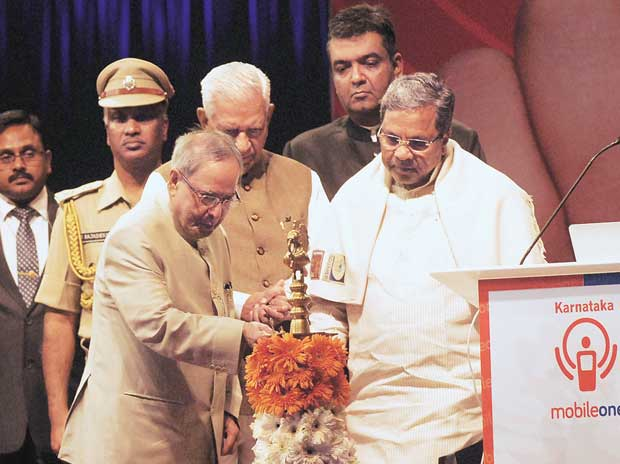 The President of India, Pranab Mukherjee, launches the Karnataka Mobile One App in Bengaluru on Monday. Also  seen are Governor Vajubhai Vala and Chief Minister Siddaramaiah