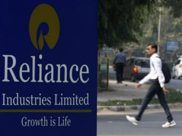 A man walks past a Reliance Industries Limited sign board installed on a road divider in Gandhinagar