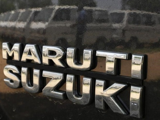 A worker is reflected on the body of a Maruti Suzuki car as he locks the door of another car at a Maruti Suzuki stockyard on Ahmedabad