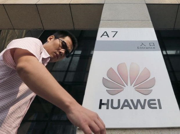 A man walks past a Huawei company logo outside the entrance of a Huawei office in Wuhan, Hubei province