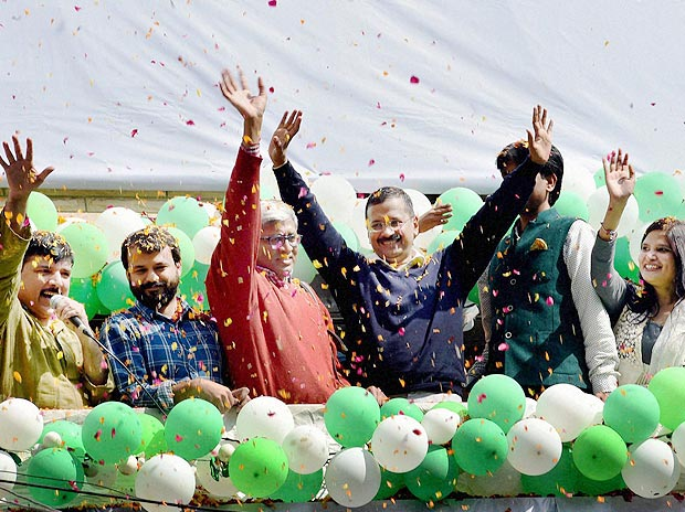 AAP convener Arvind Kejriwal, party leaders Ashutosh, Ashish Khaitan, Sanjay Singh and Kumar Vishwas wave to party volunteers as they celebrate victory in the Delhi Assembly polls, at Patel Nagar in New Delhi on Tuesday.