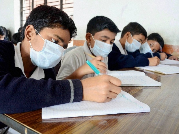School children wearing masks to prevent infection as a girl was detected Swine flu at IIIT Allahabad, in Allahabad