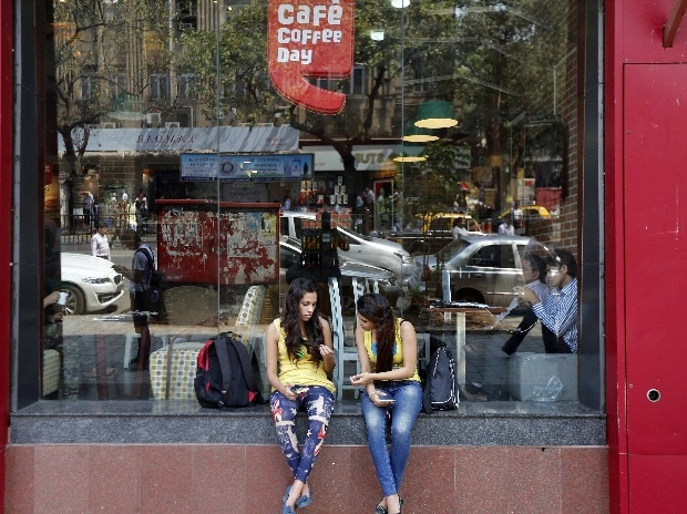 Girls sit at the window of a Cafe Coffee Day ...