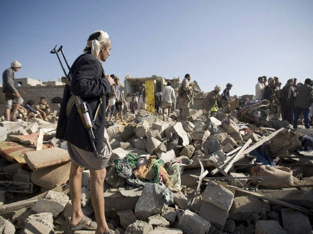 A Houthi Shiite fighter stand guard as people search for survivors under the rubble of houses destroyed by Saudi airstrikes near Sanaa Airport, Yemen