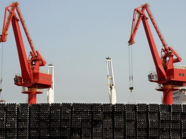 Piles of steel pipes to be exported are seen in front of cranes at a port in Lianyungang, Jiangsu province