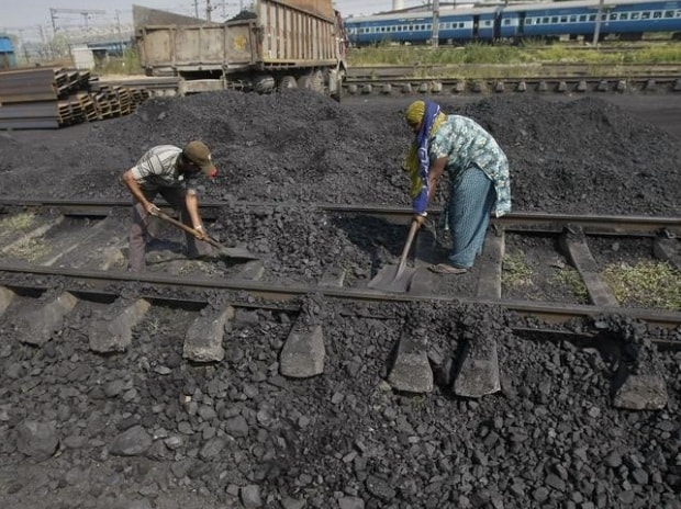 Workers clear a track in a railway coal yard on the outskirts of Ahmedabad