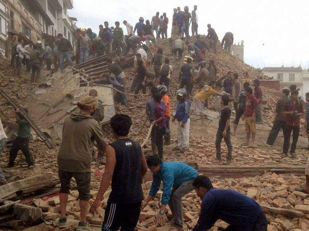 Volunteers help with rescue work at the site of a building that collapsed after an earthquake in Kathmandu, Nepal