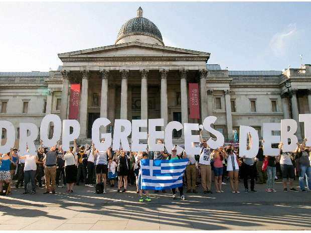 (File Photo) Demonstrators holding letters to form a banner take part in a protest against the European Central Bank, in Trafalgar Square, London, over Greece's debt repayments in 2015