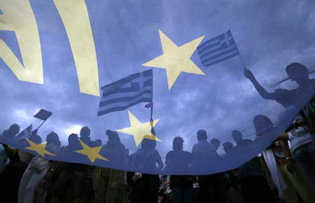 Pro-Euro protesters hold Greek national flags during a pro-Euro rally in front of the parliament building, in Athens, Greece