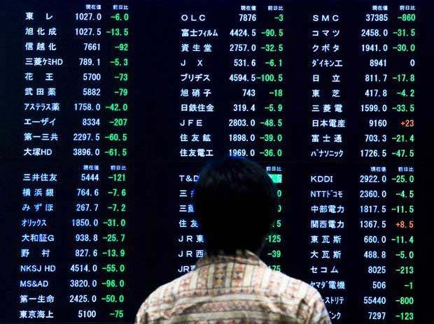 A woman stands in front of a display showing market indices at the Tokyo Stock Exchange