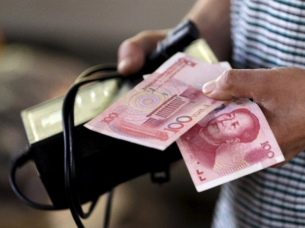 A customer holds a 100 Yuan note at a market in Beijing