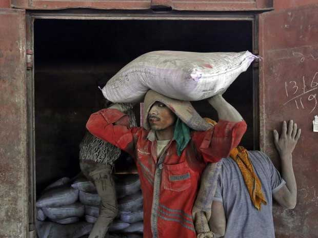 A worker unloads a sack filled with cement at a ...