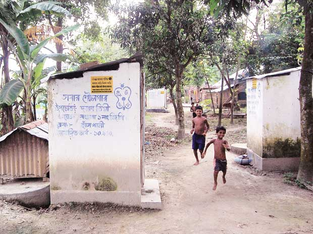 Children run past the toilets built by the state government under the Nirmal Bangla Abhijan in Bagula I in Nadia, West Bengal