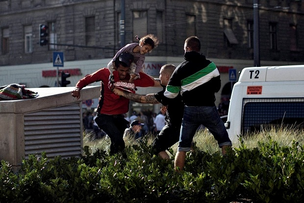 A Syrian man carrying a child (left) scuffles with a Hungarian nationalist in front of the Keleti train station in Budapest, Serbia on Friday (September 4, 2015). Minor skirmishes broke out at the Keleti train station, where hundreds of migrants and
