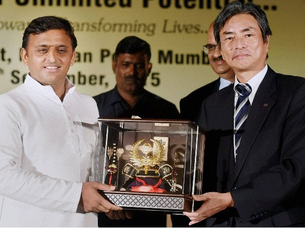 Uttar Pradesh Chief Minister Akhilesh Yadav is presented a memento by a representative of Toshiba during the Investors Conclave in Mumbai