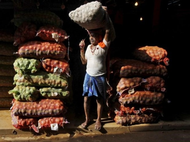 A labourer carries a sack of onions