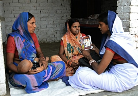 A health worker using Mobile Kunji card to guide a mother