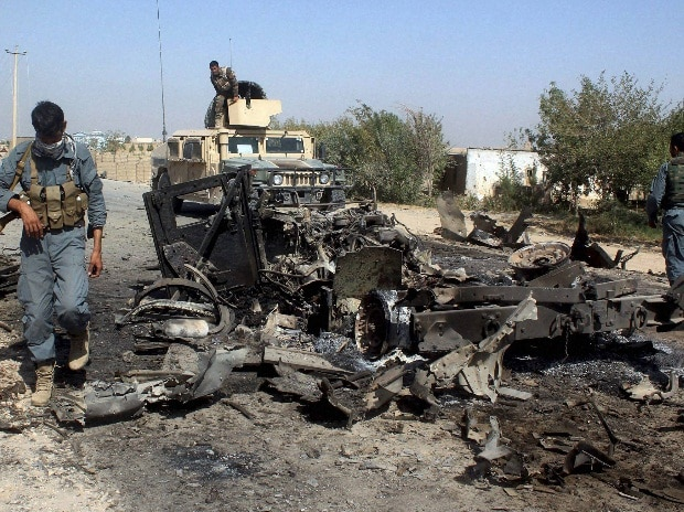 Afghan security forces inspect the site of a U.S. airstrike in Kunduz city, north of Kabul, Afghanistan