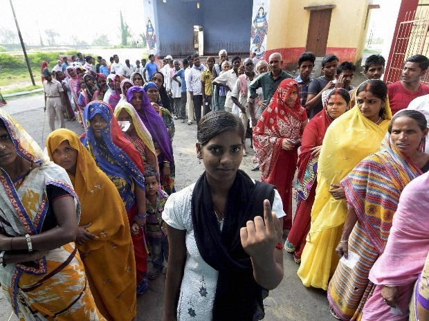 Voters wait in queues to cast their votes at a polling station in Begusarai on Monday during the first phase of Bihar assembly elections