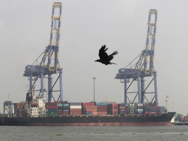 A crow flies past a container ship docked at a ...