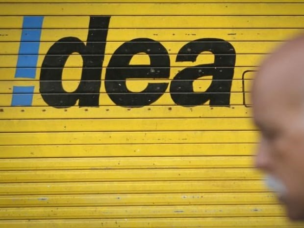A man walks past a shop displaying Idea Cellular Ltd's logo on its shutters in Mumbai