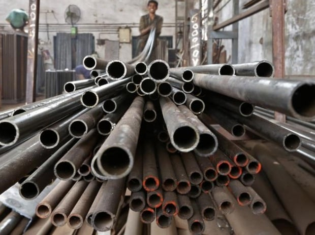 A worker stacks steel pipes in Ahmedabad