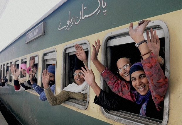 Sikh pilgrims wave from a train as they leave for Gurdwara Nankana Sahib in Pakistan to celebrate the 547th birth anniversary of Sri Guru Nanak Dev, at the Attari Railway Station. (Photo: PTI)