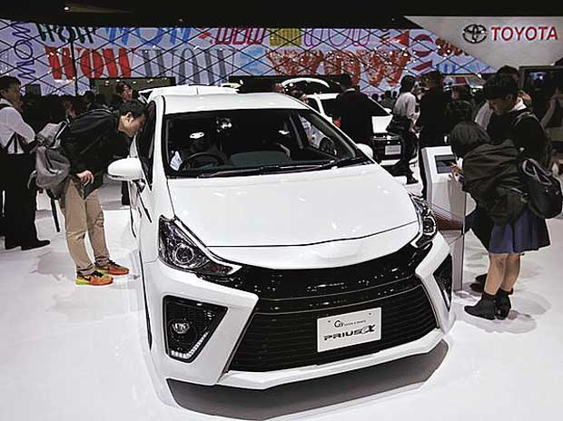 Visitors look at Toyota Motor Corp's G's Prius Alpha at the 44th Tokyo Motor Show in Tokyo