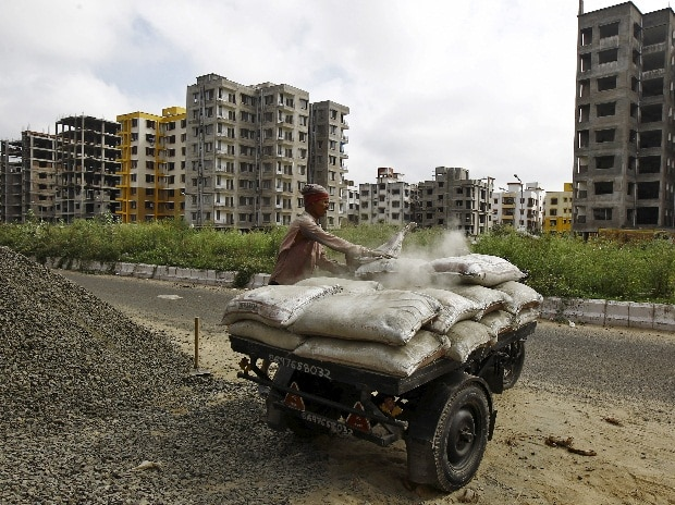 A labourer loads cement bags onto an improvised motorized rickshaw at the construction site of a residential complex on the outskirts of Kolkata