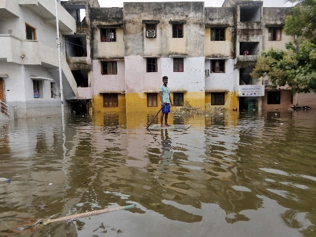 A man uses a board to float through a flooded street to reach to a market place in Chennai