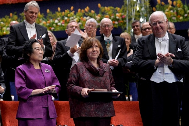 The 2015 Nobel literature laureate Svetlana Alexievich of Belarus (center) is applauded by fellow laureates Tu Youyou (left) and Angus Deaton (right) during the 2015 Nobel prize award ceremony in Stockholm on Thursday. Photo: PTI