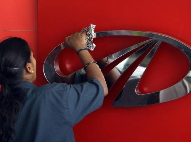 A worker cleans a logo of Mahindra & Mahindra, India's largest utility vehicles maker, inside their showroom in Chennai