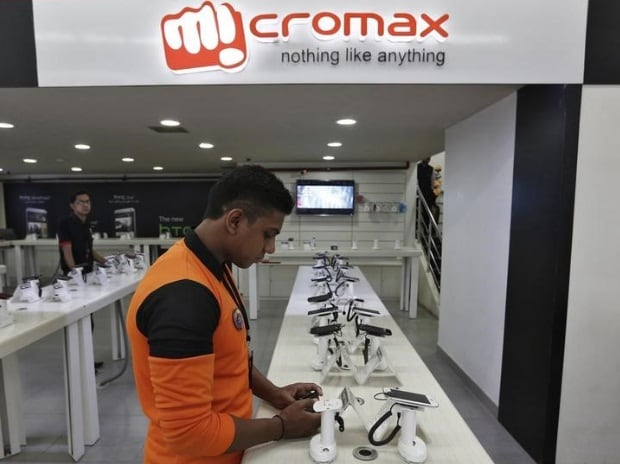 An employee stands at the counter of Micromax ...