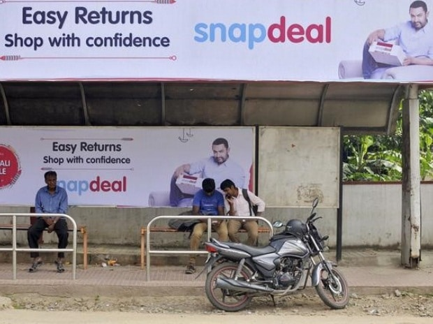 Commuters sit at a bus stop adorned with an advertisement of Indian online marketplace Snapdeal featuring Bollywood actor Aamir Khan, in Bengaluru