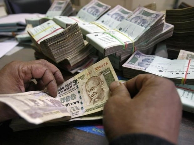 An employee counts rupee notes at a cash counter inside a bank in Agartala