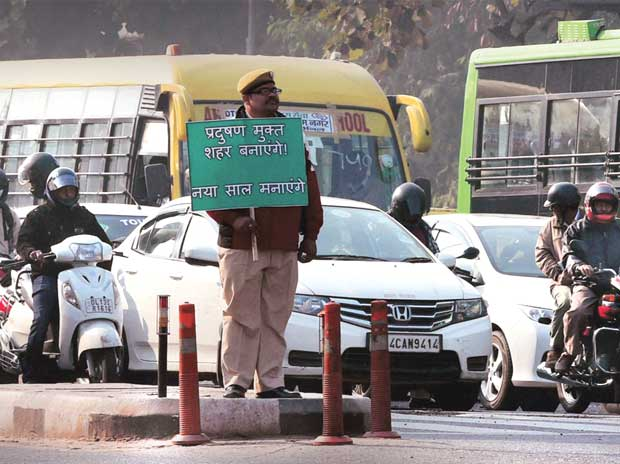 A policeman holding up a placard urging Delhiites to create a pollution-free city. Photo: PTI