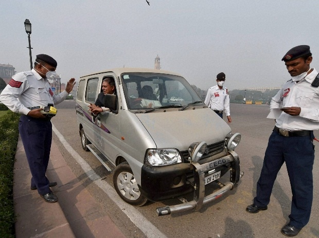Traffic policemen interceps a vehicle with an odd number and seizes it as the driver's licence had been already seized, during the trial of the 'odd-even car scheme' in New Delhi