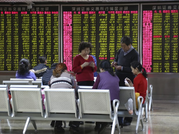 Investors play cards in front of an electronic board showing stock information at a brokerage house in Beijing, China. Photo: Reuters