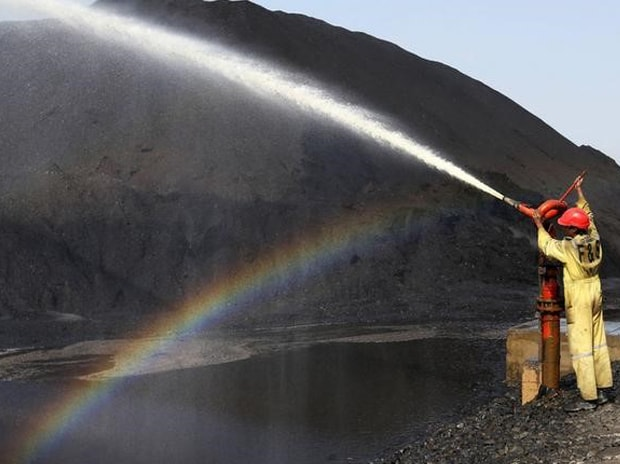 A worker sprays water over piles of coal at ...