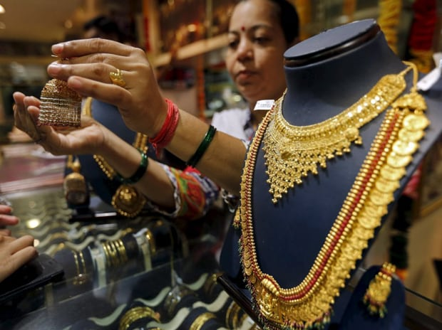 A saleswoman shows a gold earring to customers at ...
