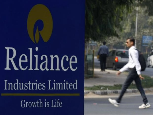 A man walks past a Reliance Industries Limited ...