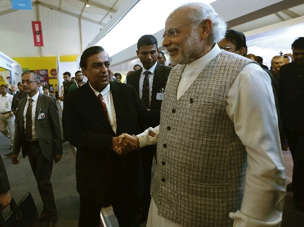 Prime Minister Narendra Modi (L) shakes hand with Mukesh Ambani, chairman of Reliance Industries Limited during a visit to a pavilion at the exhibition centre of the 'Make In India' week in Mumbai