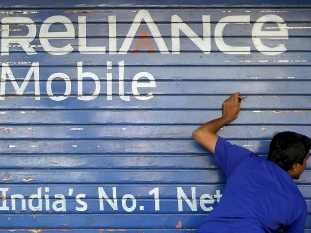 A man opens the shutter of a shop painted with an advertisement of Reliance Communications in Mumbai