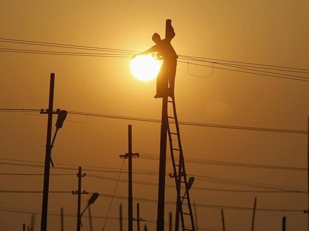 A worker is silhouetted against the setting sun while installing an overhead electric cable pole on the banks of river Ganges, Allahabad