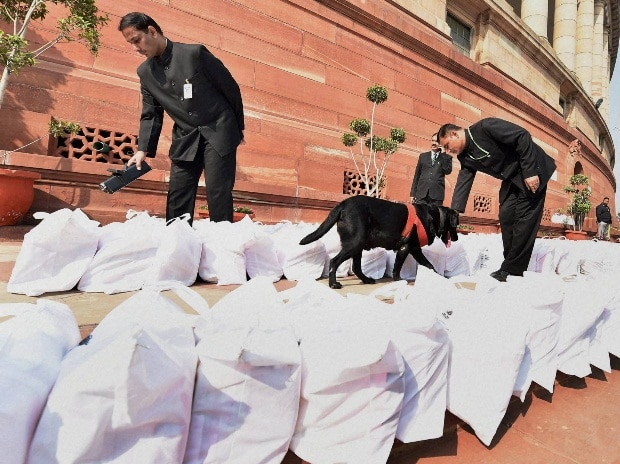 Security persons with a sniffer dog checking Rail Budget documents at Parliament house during the Budget session, in New Delhi