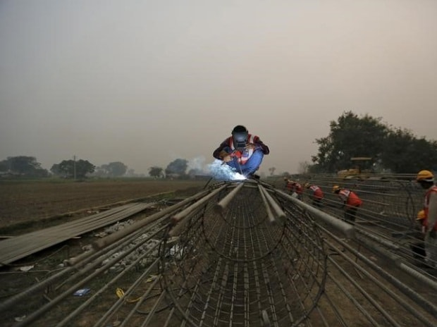 Labourers work at the construction site of a bridge being built for metro rail in New Delhi (pic: Reuters)
